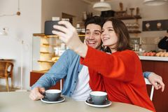 Les jeunes couples de sourire se reposant à un café ajournent ensemble Photo stock