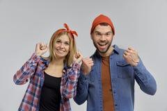 Les jeunes couples des fans étaient heureux avec serrent des poings et soulèvent vos mains dans la joie de la victoire Photographie stock libre de droits