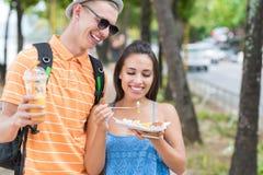 Les jeunes couples des touristes mangent de la nourriture asiatique de rue marchant dans les touristes gais homme et femme de par Image libre de droits
