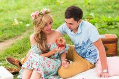 Les jeunes couples drôles d'amour la date en nature pique-niquent avec des butées toriques Images stock
