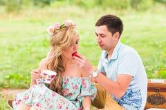Les jeunes couples drôles d'amour la date en nature pique-niquent avec des butées toriques Image stock