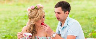Les jeunes couples drôles d'amour la date en nature pique-niquent avec des butées toriques Photo libre de droits