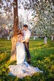 Les jeunes couples embrassant au coucher du soleil en ressort de floraison font du jardinage Amour et thème romantique Photos stock