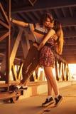 Les jeunes couples embrassant dans les fusées du coucher du soleil s'allument sur un pont c Image libre de droits