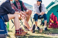 Les jeunes couples et l'ami s'asseyant sur la chaise discutent ensemble le campin Images stock