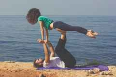 Les jeunes couples folâtres font le yoga sur la plage Photos stock