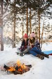 Les jeunes couples font frire des guimauves sur un feu en hiver dans une forêt sous une couverture Photo libre de droits