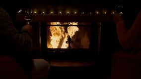 Les jeunes couples font tinter des verres à vin avec du vin blanc par la cheminée confortable banque de vidéos