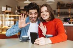 Les jeunes couples gais se reposant à un café ajournent ensemble Image libre de droits