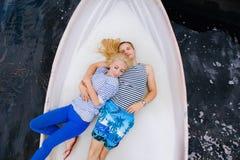 Les jeunes couples heureux étreignent se reposer dans un bateau sur le fond de lac et de ciel Photographie stock