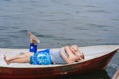Les jeunes couples heureux étreignent se reposer dans un bateau sur le fond de lac et de ciel Images stock