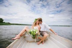 Les jeunes couples heureux étreignent se reposer dans un bateau sur le fond de lac et de ciel Images libres de droits
