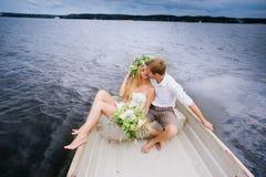Les jeunes couples heureux étreignent se reposer dans un bateau sur le fond de lac et de ciel Image stock