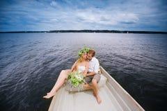 Les jeunes couples heureux étreignent se reposer dans un bateau sur le fond de lac et de ciel Photo libre de droits
