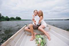 Les jeunes couples heureux étreignent se reposer dans un bateau sur le fond de lac et de ciel Photos stock