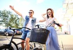 Les jeunes couples heureux allant pour un vélo montent un jour d'été dans la ville Ils ont l'amusement ensemble Photos libres de droits