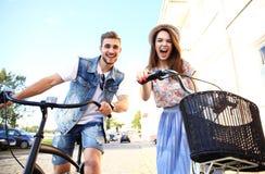 Les jeunes couples heureux allant pour un vélo montent un jour d'été dans la ville Ils ont l'amusement ensemble Images stock