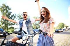 Les jeunes couples heureux allant pour un vélo montent un jour d'été dans la ville Ils ont l'amusement ensemble Images libres de droits