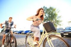 Les jeunes couples heureux allant pour un vélo montent un jour d'été dans la ville Ils ont l'amusement ensemble Photographie stock libre de droits