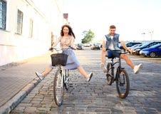 Les jeunes couples heureux allant pour un vélo montent un jour d'été dans la ville Ils ont l'amusement ensemble photographie stock