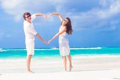 Les jeunes couples heureux au coeur de fabrication blanc forment dessus Images stock