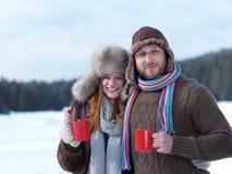 Les jeunes couples heureux boivent du thé chaud à l'hiver photo libre de droits