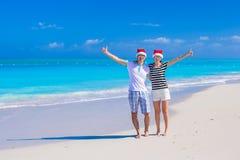 Les jeunes couples heureux dans des chapeaux rouges de Santa apprécient l'été Images stock