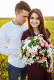 Les jeunes couples heureux dans l'amour, la fille tenant des fleurs, heureuses et s'amusent société du ` s, publicité, et texte d Image stock