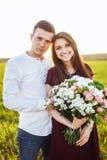 Les jeunes couples heureux dans l'amour, la fille tenant des fleurs, heureuses et s'amusent société du ` s, publicité, et texte d Images stock