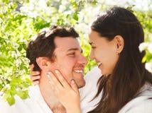 Les jeunes couples heureux dans l'amour pendant le ressort fleurissant se garent Photographie stock