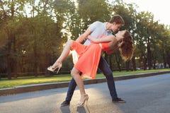 Les jeunes couples heureux dans la danse d'amour dans le coucher du soleil s'allument Images stock