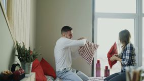 Les jeunes couples heureux et affectueux combattent des oreillers dans le lit à la maison pendant le matin banque de vidéos