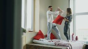 Les jeunes couples heureux et affectueux combattent des oreillers dans le lit à la maison pendant le matin clips vidéos