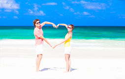 Les jeunes couples heureux faisant le coeur forment sur tropical Photographie stock libre de droits