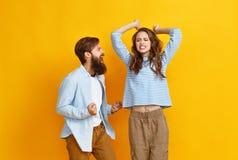 Les jeunes couples heureux ont gagné célébrer avec émotion la victoire sur le fond jaune coloré images libres de droits