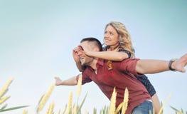 Les jeunes couples heureux ont l'amusement au champ en été, avenir heureux Images libres de droits
