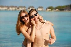 Les jeunes couples heureux ont l'amusement et détendent sur la plage La femme incite l'homme à sourire tenant des joues avec des  Photographie stock