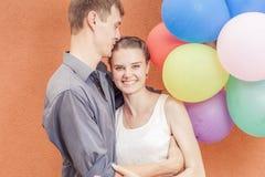 Les jeunes couples heureux près du mur orange se tiennent avec des ballons Photographie stock