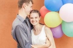 Les jeunes couples heureux près du mur orange se tiennent avec des ballons Photo stock