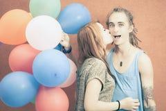 Les jeunes couples heureux près du mur orange se tiennent avec des ballons Image libre de droits