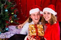 Les jeunes couples heureux s'approchent d'un arbre de Noël Photographie stock libre de droits