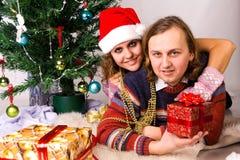 Les jeunes couples heureux s'approchent d'un arbre de Noël Photo stock