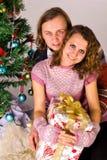 Les jeunes couples heureux s'approchent d'un arbre de Noël Image stock