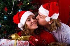 Les jeunes couples heureux s'approchent d'un arbre de Noël Images stock