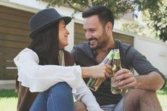 Les jeunes couples heureux se reposant dans la ville garent la bière potable, obtiennent le pain grillé Images stock