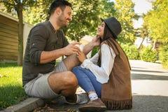 Les jeunes couples heureux se reposant dans la ville garent le café potable et shar Images libres de droits