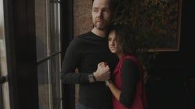 Les jeunes couples heureux se tiennent près de la fenêtre panoramique dans le café banque de vidéos