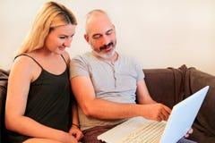 Les jeunes couples heureux utilisant l'ordinateur portable dans le divan et apprécient à la maison Photo stock