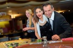 Les jeunes couples jouant le tisonnier ont le bon temps dans le casino Photo libre de droits