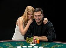 Les jeunes couples jouant le tisonnier profitent d'un agréable moment dans le casino Image libre de droits